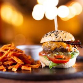 Burger hovězí | Mletý hovězí chuck roll, čedar, slaninový chips, nakládaný okurek, rajče, okurkový relish,barbecue omáčka a salát a to vše v naší sezamové housce s batátovými hranolkami a aioli omáčkou.