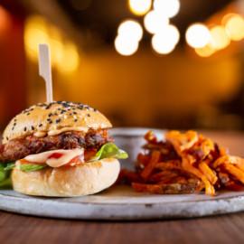 Indický fazolový burger | Burger ze směsi fazolí a pečené zeleniny s indickým kořením Chat Masala, rajče, sweet chilli omáčka, červená cibule a salát s batátovými hranolkami a sweet chilli majonézou.