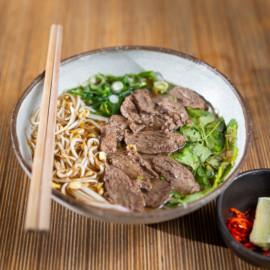 Pho Bo | Vietnamský hovězí vývar s kořením (čínský badyán, černý kardamon), tažený 15 hodin na 92° s hovězími plátky chuck roll, rýžovými nudlemi pho, perilou, koriandrem, mungo klíčky, šalotkou a jarní cibulkou.