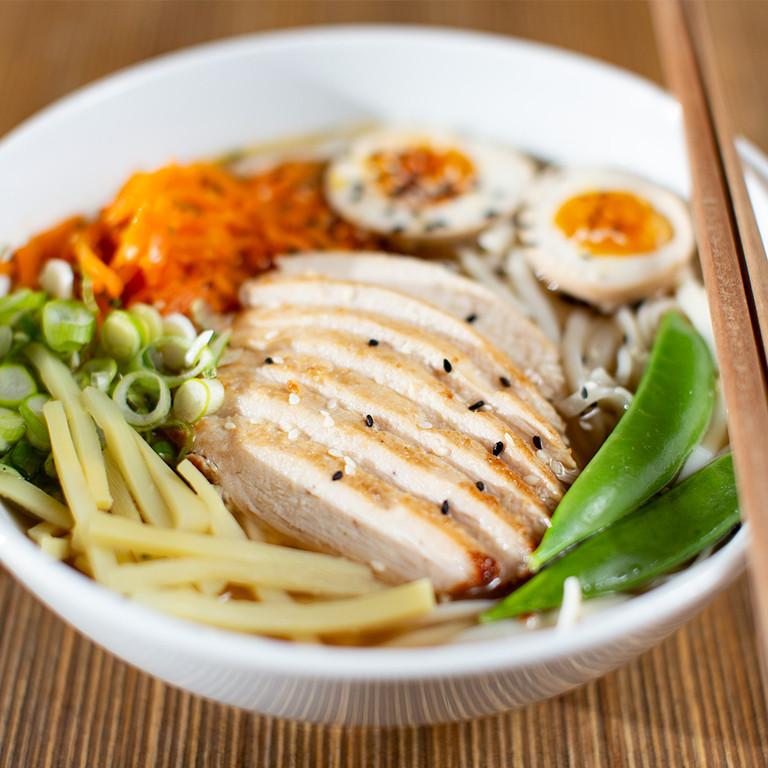 Japonský Ramen (dlouze tažený silný kuřecí vývar s filírovaným kuřecím prsem, vejcem nakládaným v saké a sójové omáčce, s nudlemi, jarní cibulkou, hráškovými lusky, bambusem a mrkví julienne restovanou na sezamovém oleji)
